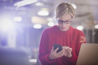 132122 Businesswoman working late at laptop texting with cell phone in dark office-1